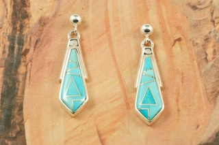 Genuine Sleeping Beauty Turquoise inlaid between ribbons of Sterling Silver. Beautiful Sterling Silver Post Earrings feature precision channel inlay. Designed by Navajo Artist Calvin Begay. Signed by the artist.